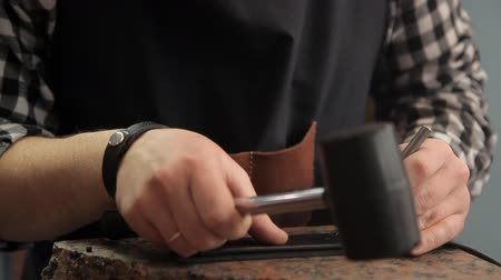 přezka : The master makes holes in the leather belt. Leather belt manufacturing