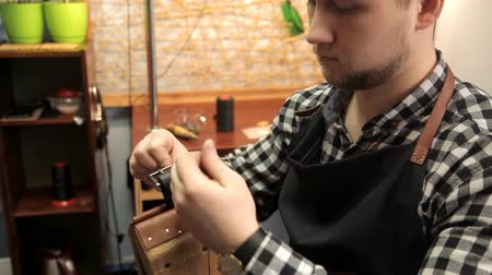 reptilian : The master fastens the buckle on the leather belt, sews a needle. Procedure for the manufacture of leather belts