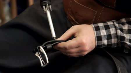desenli : The master fastens the buckle to the leather belt. Procedure for manufacturing leather belts