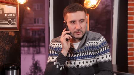 харизматический : Charismatic young man drinks coffee and communicates by phone in a restaurant