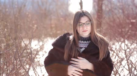 suszarka : Cute girl with glasses and mink fur coat and straightening hair outside in winter