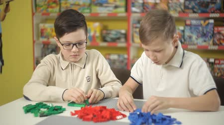 letec : Two boys erect buildings from a childrens plastic designer Dostupné videozáznamy