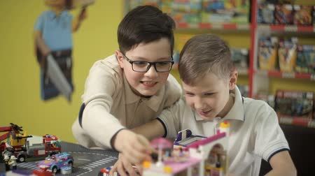 letec : In the toy store, two boys are building structures from cubes of a plastic designer