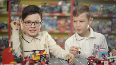 letec : Two boys play with objects made of plastic designer