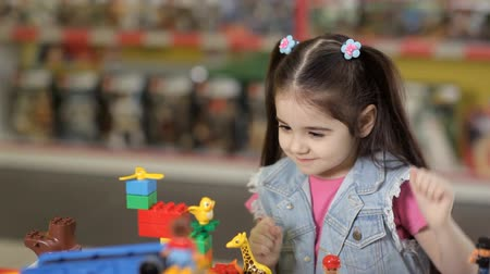 головоломки : Cute little girl is playing with objects made of plastic elements, blocks of childrens designers