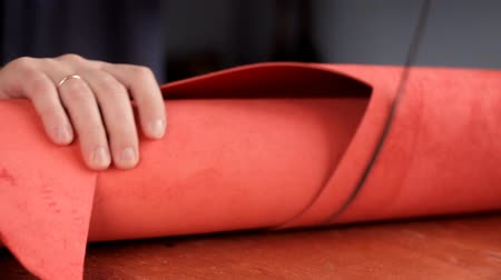 přezka : Master unwinds a roll of red leather for the production of leather goods