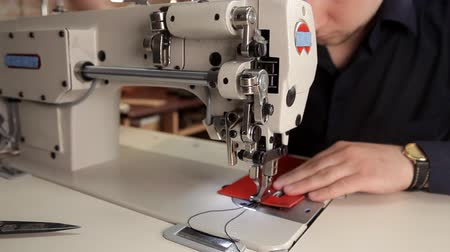 pasek : In the workshop, a man sews real leather with a sewing machine. Procedure for the manufacture of leather products Wideo