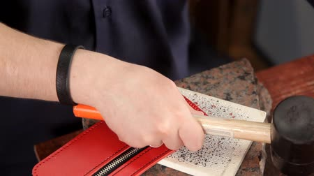 пятна : The man punches the holes in the leather blank with a hammer and a special tool