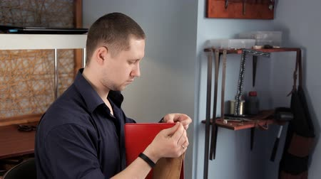 brim : In the workshop, a man is sewing leather workpieces, making a wallet