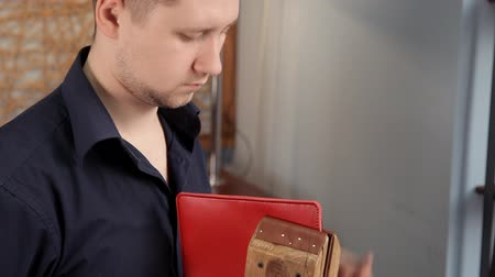 çivit : In the workshop, a man is sewing leather workpieces, making a wallet