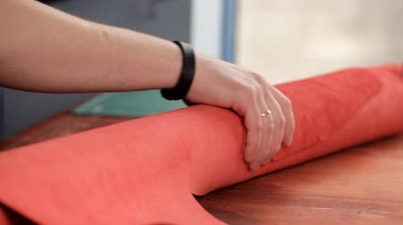 spona : Master unwinds a roll of red leather for the production of leather goods