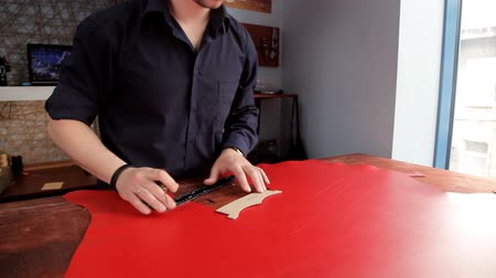 szewc : Craftsman makes a line of markings on the red leather cloth Wideo