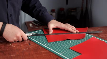 etli : From a red leather layer the man cuts out preparations of skin, using a leather knife and a ruler