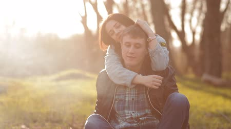 кемпинг : A pair of lovers sit together near a fire in nature. Romantic pastime