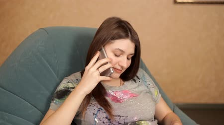 elite : Pregnant girl sitting in an armchair by the fireplace and talking on the phone Stock Footage