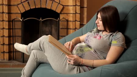 fotel : Happy pregnant girl sits in a chair by the fireplace and reads a book, stroking her belly
