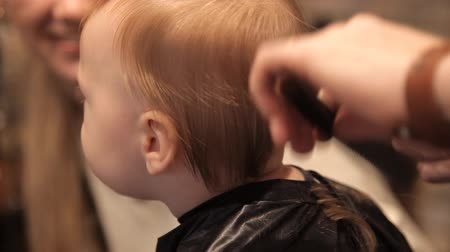 first person : In a brutal hairdressers, a young child is being sheared by a clipper Stock Footage