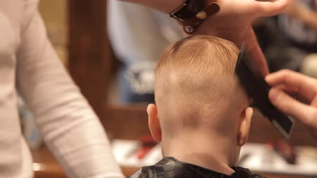 barber hair cut : Small child is placed hair after haircut Stock Footage