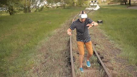 опыт : A young man is on the rails for rail transport in a virtual reality helmet.View images, video games.The world of virtual reality Стоковые видеозаписи