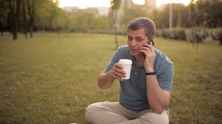 egyiptomi : A man sitting on the lawn in a green Park on a summer day at sunset drinking a drink and talking on the phone Stock mozgókép