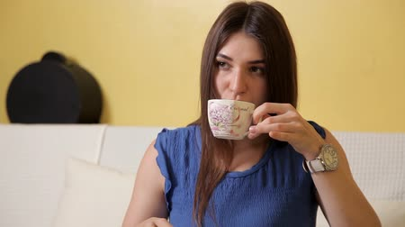 without face : A young girl in a blue suit is sitting on the couch and is drinking tea thinking about something. Tea drinking
