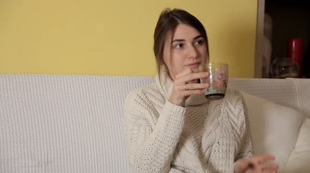 happy socks : A young girl in a cozy warm sweater on a winter evening at home drinking tea and thinking about something