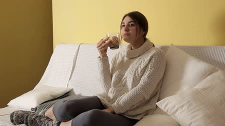 fireplace : A young girl in a cozy warm sweater on a winter evening at home drinking tea and thinking about something