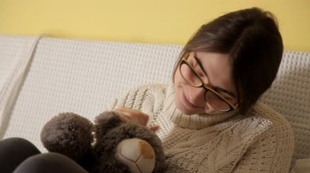 sentiment : A young girl in a white sweater and wearing glasses is played with a soft toy. Childhood. Toys
