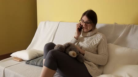 mascot : A young girl in a white sweater and wearing glasses plays with a soft toy, speaks on the phone. Toys