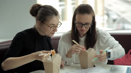кафетерий : Two young business girls are sitting in a cafe, eating Chinese noodles and discussing business development. Work.Eating