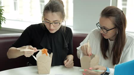 латте : Two young girls are sitting in a cafe, eating Chinese noodles and planning business development