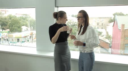 голова и плечи : Two young business girls drink coffee at the window in the business center and communicate.Work, coffee, lunch Стоковые видеозаписи