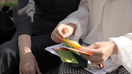 freelance work : Two young business girls in the summer sitting in the Park near the business center and consider the color cards.Cutaways