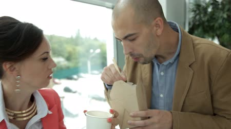 visto : Young business girl and young business guy are drinking coffee and eating noodles at work. Work, food, lunch Stock Footage