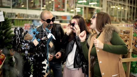people shopping : cheerful smiling funny friends glasses were measured in the christmas store Stock Footage