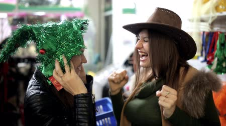 мишура : two friends in the store laughing wear funny hats and dancing Стоковые видеозаписи
