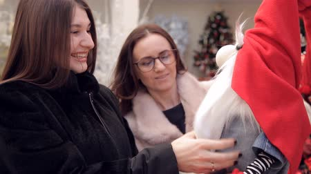placeholder : two women playing with a Christmas gnome in the store