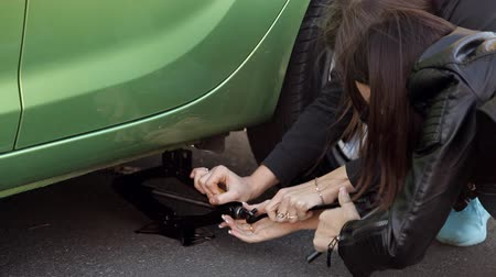 yol kenarı : Girls the side of the road learn to change the tyre on his car