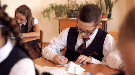 tanítvány : boy in uniform at school in the classroom makes the paper plane