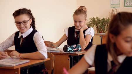 spolužáci : schoolgirl in the form of debits on the lesson around indulge classmates