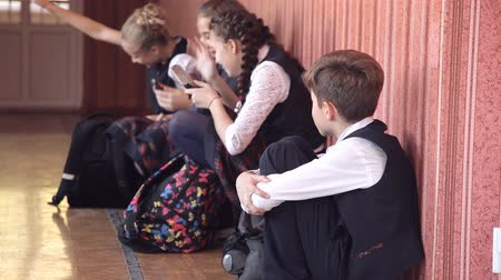 recess : Selective focus of miserable schoolboy in uniform sitting alone on floor in school hallway with head on knees crying and feeling lonely, chatting and laughing classmates in background