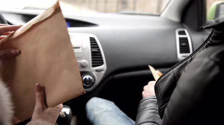 evidência : Selling secrets. A spy or a private detective sends a package of documents to the woman buyer in the car and gets in return the envelope with money, close-up