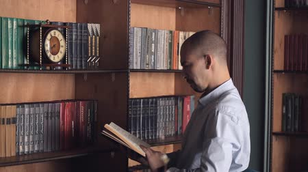 acadêmico : Choice and decision concept. Man makes choice standing in library. A man chooses a book to reading in a library Stock Footage