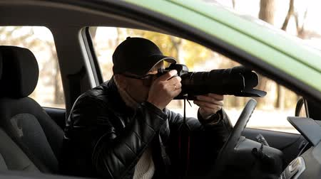 investigador : A private detective or a spy conducts surveillance of the object of surveillance. A man secretly taking pictures from the car window