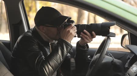 fbi : A private detective or a spy conducts surveillance of the object of surveillance. A man secretly taking pictures from the car window