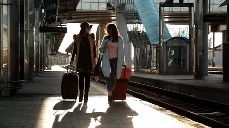 sentiment : Two girls at the railway station with their suitcases out on the platform waiting for the train
