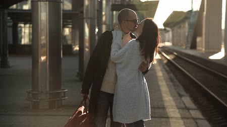 departing : Romantic couple kissing and hugging in train station before separation
