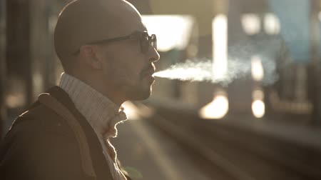 impatience : Business man in a raincoat and sunglasses smokes a cigarette on the platform of the railway station waiting for a train Stock Footage