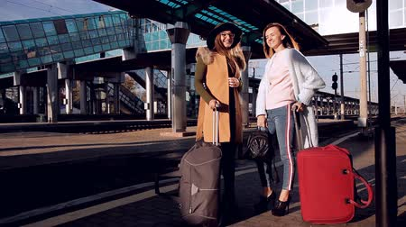 оставлять : Two girls at the railway station with their suitcases out on the platform waiting for the train