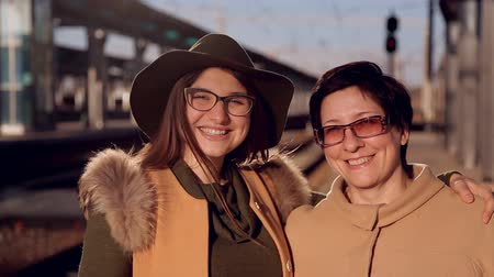 ölelés : mom and adult daughter in glasses at the railway station look at the camera and smile at the video portrait Stock mozgókép
